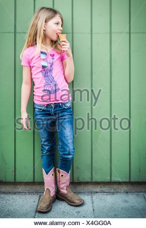Portrait of young girl eating icecream - Stock Photo
