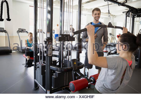 Woman doing lat pulldown exercise at gym - Stock Photo