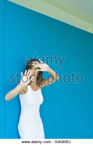Woman leaning against wall, holding hands up in front of face, looking at camera - Stock Photo