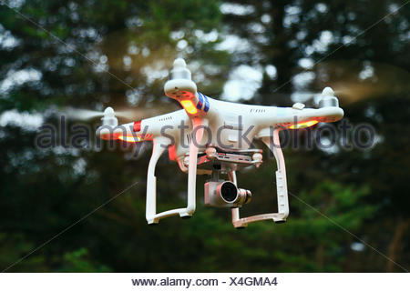 Drone hovering in the air against a woodsy background. - Stock Photo