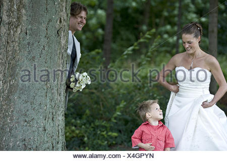 Groom playing hide and seek with his son - Stock Photo