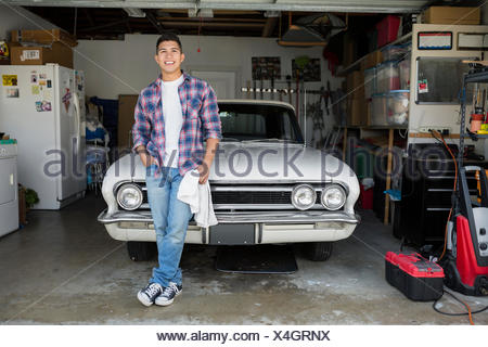 Portrait smiling young man with vintage car garage - Stock Photo