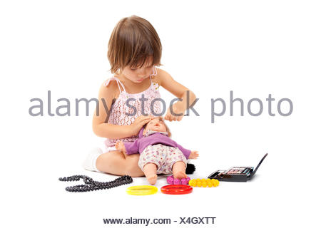 Beautiful little girl paints cosmetics doll - Stock Photo