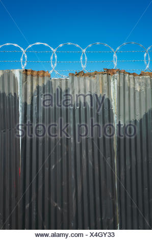 Worn corrugated metal fence, razor wire above Stock Photo