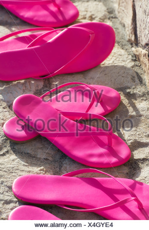 Matching pairs of hot pink sandals. - Stock Photo