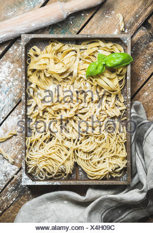 Various homemade fresh uncooked Italian pasta with flour and green basil leaves in wooden tray over shabby background, top view, - Stock Photo