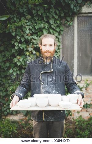 Front view of bearded mid adult man holding tray with clay pot looking at camera smiling - Stock Photo