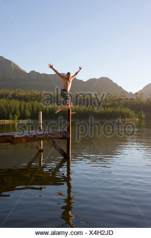 Man in swimming shorts jumping from jetty into lake arms up showing off smiling - Stock Photo