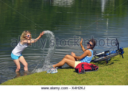 a young woman standing in shallow water and splashing water to her friend, France, Savoie - Stock Photo