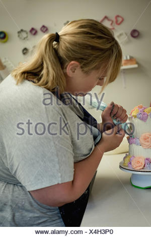 Woman decorating cake in the kitchen at home - Stock Photo