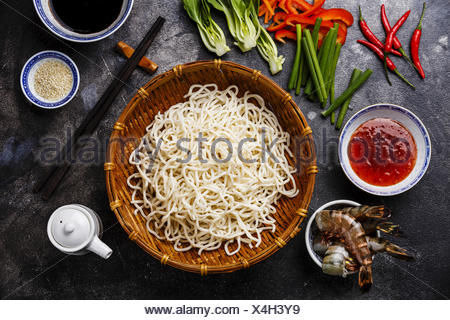 Raw Udon noodles in bamboo basket and Ingredients for cooking asian food with Tiger shrimps, greens, vegetables, spices on dark background - Stock Photo