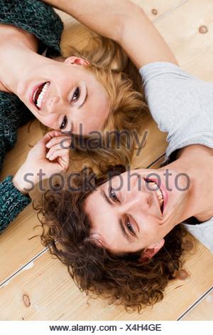 Studio shot couple lying on floor - Stock Photo