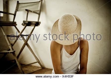 Mexico; Woman covering her face with hat - Stock Photo