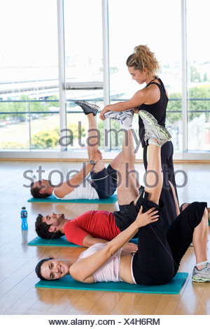 Female fitness instructor teaching class in studio in gym, hands on man's foot, portrait of woman smiling - Stock Photo