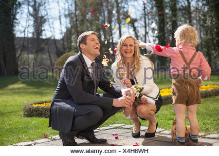 Son throwing flower petals on bride and groom, Munich, Bavaria, Germany - Stock Photo