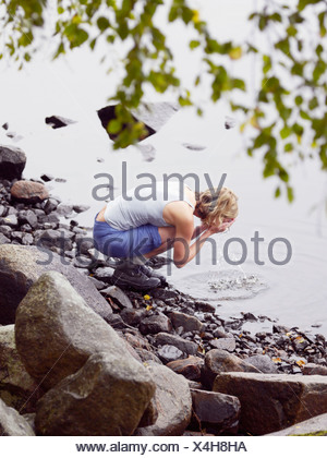 Woman washing face in lake. - Stock Photo