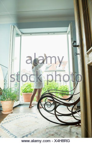 Senior woman stretching her body near window - Stock Photo