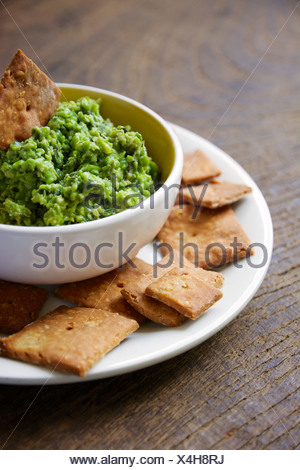 Bowl of dip made from peas, rocket salad, mint and soy yogurt with home-made crackers - Stock Photo