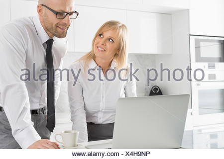 Happy business couple working on laptop in kitchen - Stock Photo