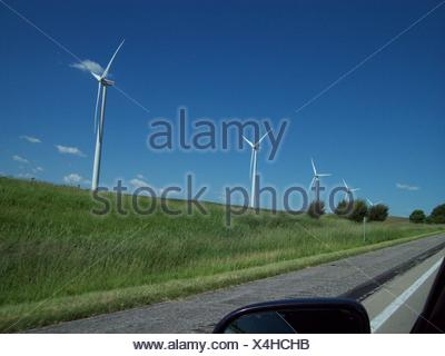 Wind Turbines On Road Against Clear Sky - Stock Photo
