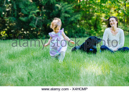 Female toddler running away from mother in park - Stock Photo