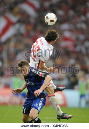 Tackling, Christian Traesch, German footballer playing for VfB Stuttgart, above, versus Ivica Olic, playing for HSV, Hamburger  - Stock Photo