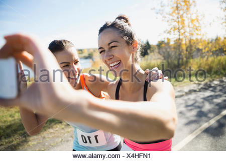 Laughing runners taking selfie on sunny path - Stock Photo