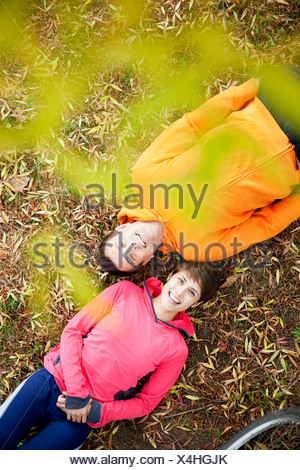 Man and woman lying on grass in the park - Stock Photo
