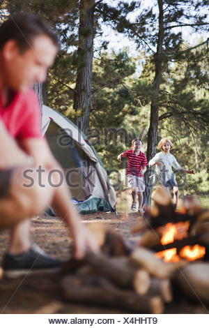 Children running to father in campsite - Stock Photo