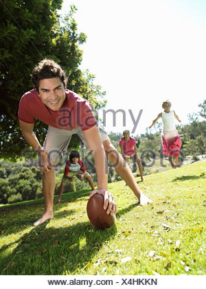 Family playing american football in park focus on man in foreground surface level tilt - Stock Photo