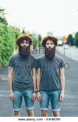 Portrait of identical adult male twins with red hair and beards on sidewalk - Stock Photo
