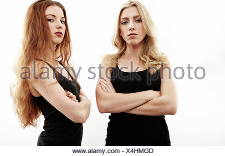 Studio portrait of two young woman with arms folded - Stock Photo