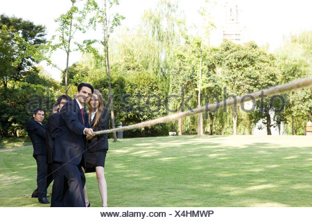 Five business people pulling a rope on the lawn - Stock Photo