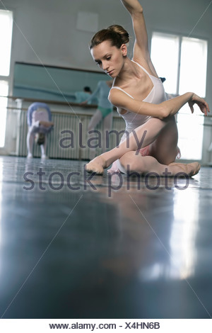 A female ballet dancer sitting in pose on the floor - Stock Photo