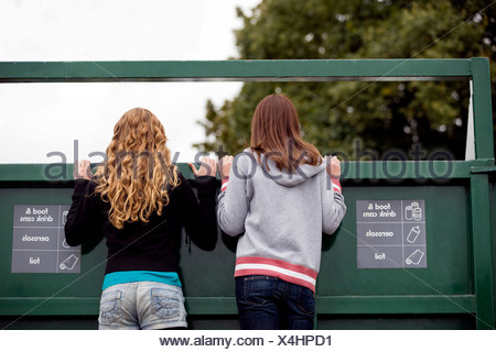 Two teenage girls looking into a recycling container - Stock Photo
