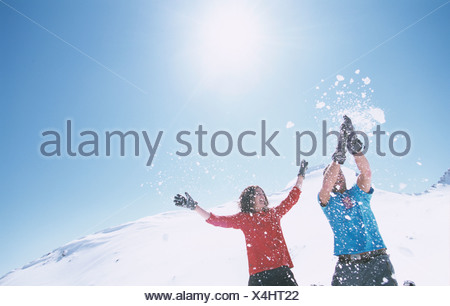 Young couple playing in snow, low angle view - Stock Photo