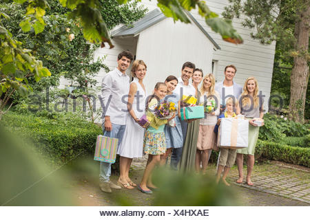 Portrait of three generation family in garden with birthday gifts - Stock Photo