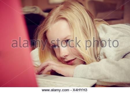 Young girl lying on floor using laptop - Stock Photo