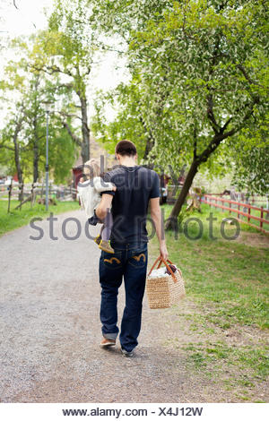 Sweden, Uppland, Father walking with daughter (18-23 months) - Stock Photo