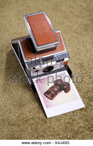 A Polaroid camera with a Polaroid picture of a digital camera - Stock Photo