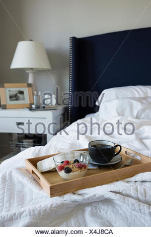 Breakfast on tray on bed in bedroom - Stock Photo