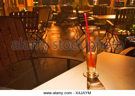 Drink in a glass with straw in an empty restaurant - Stock Photo