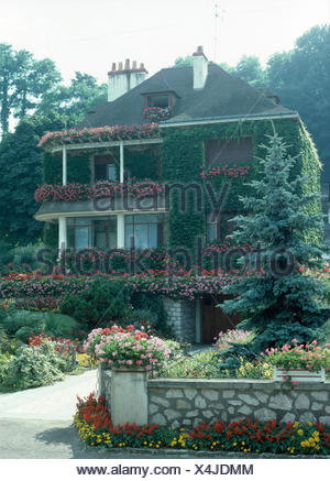 Exterior of a French country house with profusely flowering geraniums in window boxes on the balconies - Stock Photo