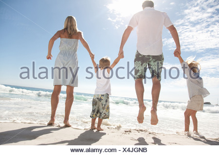 Family holding hands and jumping on beach - Stock Photo