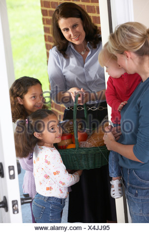 Knoxville, Tennessee,United States Of America; A Woman With Her Daughters Delivering Food In A Basket To A Woman With a Child - Stock Photo