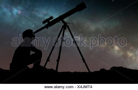 Artwork of a boy looking through a telescope, seen in silhouette against the star clouds of the Milky Way. The boy is using a refracting telescope. - Stock Photo