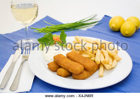 Fish sticks, tartar sauce and french fries served with a glass of white wine, lemons and chives - Stock Photo