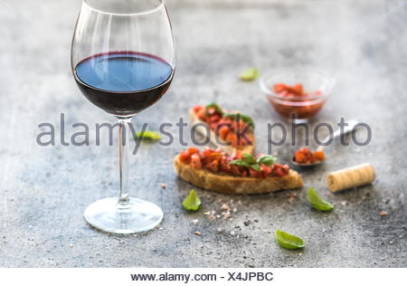 Glass of red wine and canapes with tomatoes and basil, selective focus, horizontal composition - Stock Photo