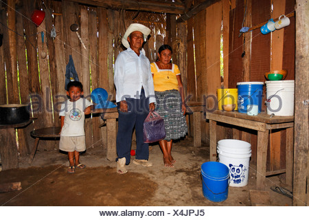 Mayan woman, man, small boy, one-room flat, plastic bucket, wooden hovel, Punta Gorda, Belize, Central America - Stock Photo