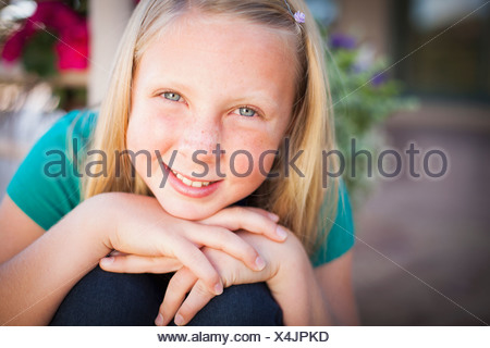 A child, a young girl sitting leaning forward and smiling. Her chin resting on her hands. - Stock Photo